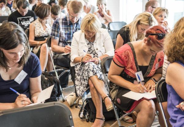 De deelnemers van de inspiratiebijeenkomst schrijven op een ansichtkaart hun eerste stap om regeldruk aan te pakken. In september verstuurt Kennisland de ansichtkaarten als reminder.