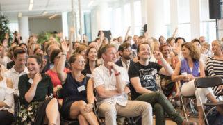 Een zaal vol enthousiaste deelnemers