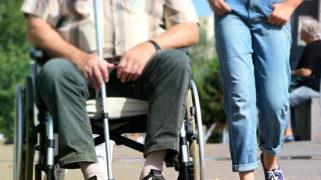 Meisje loopt naast man in rolstoel