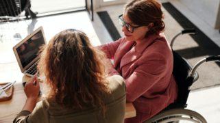Vrouw in rolstoel met laptop